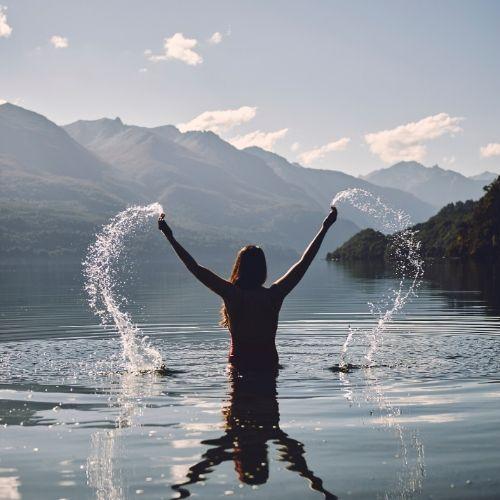 Donna immersa in acqua a mezzo busto sparge acqua in aria con le braccia