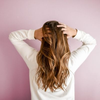 foto di una donna di spalle mentre si passa la mano tra i capelli