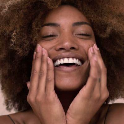 Primo piano di una giovane donna che utilizza il cloruro di magnesio per idratare la pelle del viso