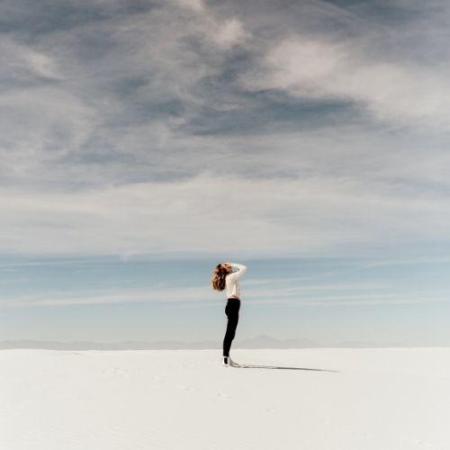 Donna in spiaggia si dispera a causa dei dolori provocati dal ciclo mestruale