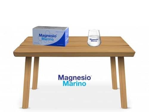 Tavolo di legno illustrato con appoggiati sopra un confezione di Magnesio Marino® con bicchiere brandizzato