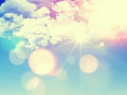 Fasci di luce solare che emergono da dietro le nuvole in un cielo azzurro