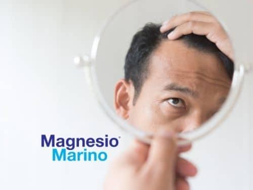 Uomo guarda allo specchio la stempiatura dei capelli