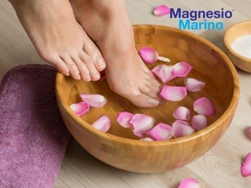 Foto di una donna che immerge i piedi in acqua e Magnesio Marino®