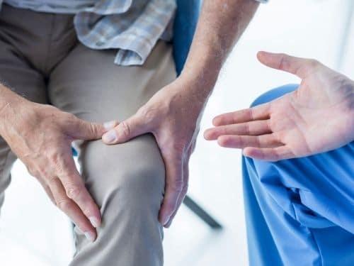 Signore si tiene il ginocchio a causa del forte dolore