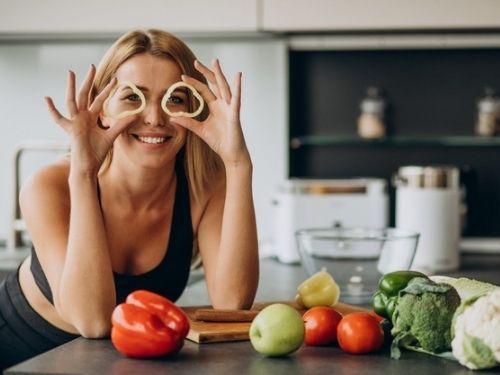 Ragazza appoggiata con i gomiti su di un tavolo con frutta e verdura distribuita dinanzi a lei