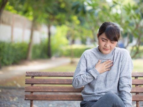 donna seduta sulla panchina con il bruciore di stomaco