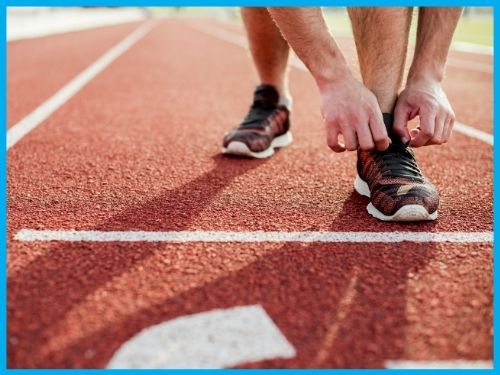 Runner intento ad allacciarsi le scarpe sulla pista di atletica